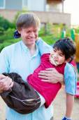 Caucasian father carrying biracial disabled son on playground — Stock Photo