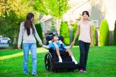 Disabled little boy in wheelchair walking with sisters on glassy — Stockfoto
