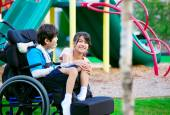 Sister sitting next to disabled brother in wheelchair at playgro — Stok fotoğraf