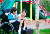 Sister sitting next to disabled brother in wheelchair at playgro — Stock Photo