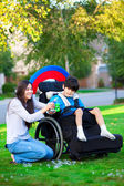 Biracial older sister playing outdoors with disabled little brot — Stock Photo