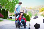 Caucasian father helping disabled biracial son in wheelchair pla — Stock Photo