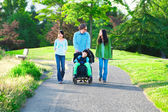 Disabled boy in wheelchair walking with family outdoors on sunny — Stock Photo