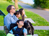Disabled boy in wheelchair with family outdoors on sunny day sit — Stock Photo