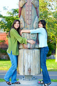Two young, biracial teen girl in park hugging a totem pole on su — Stock Photo