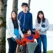 Disabled little boy in wheelchair surrounded by brother and sist — Stock Photo #63351371