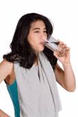 Beautiful biracial teenage girl drinking water while exercising — Stock Photo