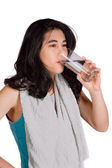Beautiful biracial teenage girl drinking water while exercising — Foto de Stock