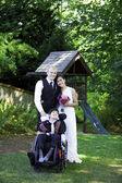 Interracial bride and groom standing with her disabled little bo — Stock Photo
