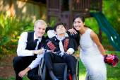 Biracial bride and groom with her little disabled brother in whe — Foto de Stock