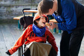 Father feeding disabled son a hamburger in wheelchair. Child has — Stock Photo