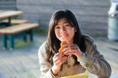 Young biracial teen girl outdoors eating hamburger — Foto de Stock