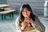 Young biracial teen girl outdoors eating hamburger — Stock Photo