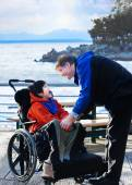 Handsome father talking with disabled biracial son outdoors by l — Stock Photo