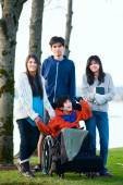 Disabled little boy in wheelchair surrounded by brother and sist — Stock Photo