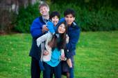Disabled biracial child riding piggy back on his sister, family  — Stock Photo