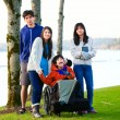 Disabled little boy in wheelchair surrounded by brother and sist — Stok fotoğraf #65551027