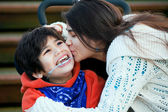 Big sister kissing disabled little brother seated in wheelchair — Stock Photo