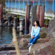Young teen girl sitting on large boulders along lake shore, look — Stock Photo #72431145