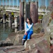 Young teen girl sitting on large boulders along lake shore, look — Stock Photo #72431173