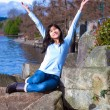 Young teen girl arms raised while sitting on large rock along la — Stock Photo #72431259