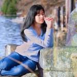 Young teen girl sitting outdoors on rocks praying — Stock Photo #72431291