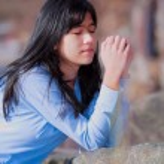 Young teen girl sitting outdoors on rocks praying — Stock Photo #72431319