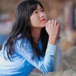 Young teen girl sitting outdoors on rocks praying — Stock Photo #72431329