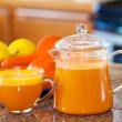One cup of orange colored juice on kitchen counter with fruit an — Stock Photo #72431501