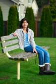 Young biracial teen girl relaxing outdoors on park bench — Stock Photo