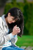 Young biracial teen girl praying outdoors on bench — Stock Photo