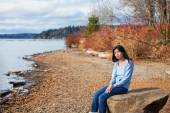 Young teen girl in blue shirt and jeans sitting along rocky lake — Stock Photo