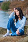 Young unhappy teen girl sitting on rocks along lake shore, looki — Stockfoto