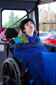 Disabled eight year old boy in wheelchair buckled on school bus — Stock Photo