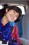 Disabled little boy sitting in carseat inside vehicle — Stock Photo