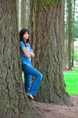 Young teen girl leaning against large pine tree trunk, sad — Stock Photo