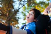 Handsome little disabled boy in wheelchair, enjoying sunset at p — Stock Photo