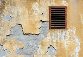 Wall crumbling plaster coat and rusty ventilation grid — Stock Photo