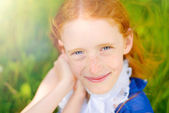 Red-haired girl in a sunny garden — Stock Photo