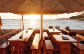 Terace restaurant tables under parasol at sunset — Stock Photo