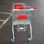 Metal trolley shopping basket at asphalt background — Stock Photo #69822033