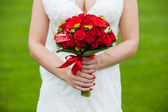 Bride with red wedding bouquet in hand — Stock Photo