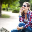 Young pretty woman talking on mobile phone profile, in autumn park — Stock Photo #54374469