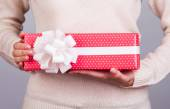 Female hands holding gift box with ribbon. — Stock Photo