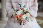 Beautiful wedding bouquet of roses in hands of bride. — Stock Photo