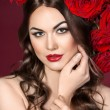Beautiful Fashion Model Girl Portrait with big red roses in hair — Stock Photo #72784097