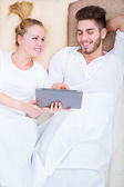 Young couple with a tablet PC in bed — Stock Photo