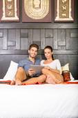 Young couple using a Tablet PC in a asian hotel room — Stock Photo
