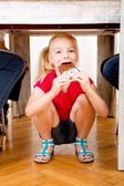 Girl eating chocolate beneath table — Stock Photo