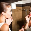 Beautiful young woman putting on makeup in the bathroom — Stock Photo #68573711